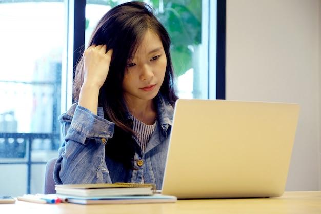 Jonge aziatische vrouw met gefrustreerde uitdrukking terwijl het werken met laptop Premium Foto