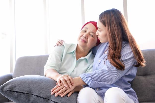 Jonge aziatische vrouw met haar moeder die een hoofddoek draagt en vecht tegen kanker, zit op de bank en haar arm om haar moeder geslagen. Premium Foto