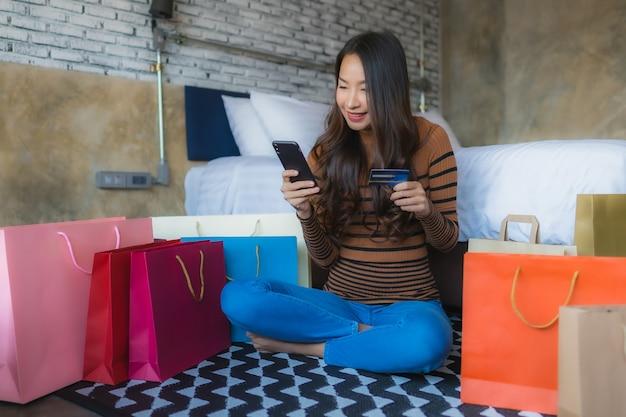 Jonge aziatische vrouw met slimme mobiele telefoon en laptop computer die creditcard voor online het winkelen gebruikt Gratis Foto
