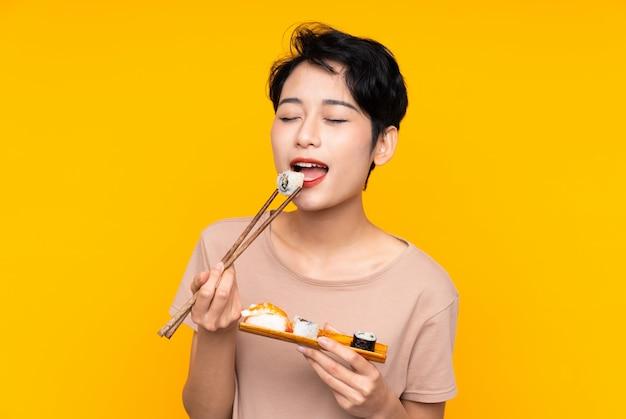 Jonge aziatische vrouw met sushi over gele achtergrond Premium Foto