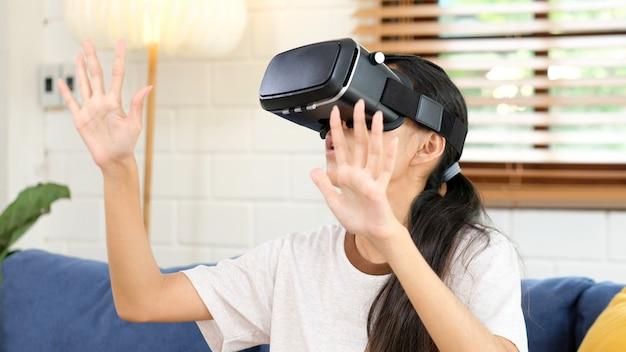 Jonge aziatische vrouw opwindend in vr-headset opzoeken en proberen objecten in virtual reality thuis woonkamer aan te raken, tienermeisje spelen vr-headset, mensen en vrije tijd virtual reality-technologie Premium Foto