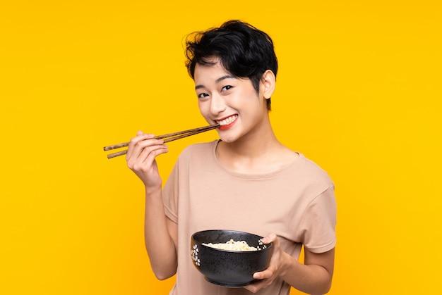 Jonge aziatische vrouw over geïsoleerde gele muur die een kom van noedels met eetstokjes houdt Premium Foto