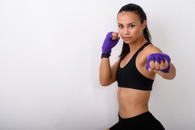 Jonge aziatische vrouw vechter met boksen wraps klaar om te vechten tegen witte ruimte Premium Foto
