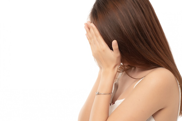 Jonge aziatische vrouw verbergt haar gezicht; mislukt meisje doet facepalm; aziatische volwassen zakenvrouw. Premium Foto