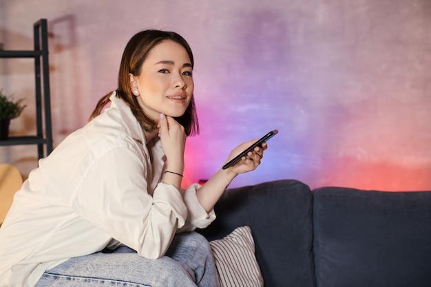 Jonge aziatische vrouw zittend op een bank in een gezellige kamer kijkt naar de camera Premium Foto