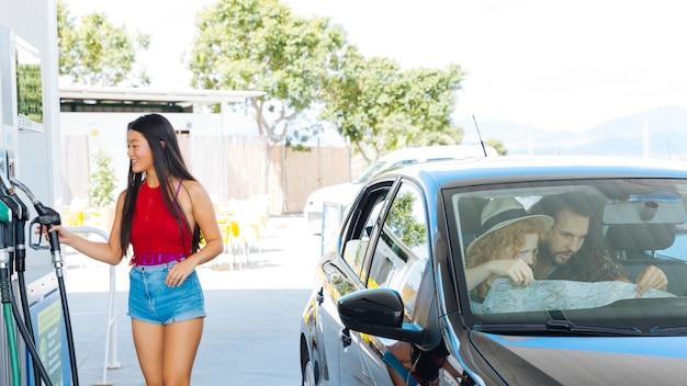 Jonge aziatische vrouwelijke nemende benzinepomppijp terwijl vrienden die kaart onderzoeken Gratis Foto