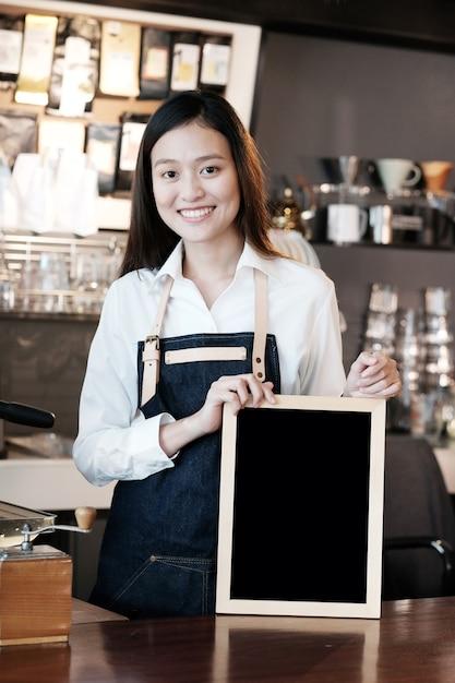 Jonge aziatische vrouwen barista die leeg bord met het glimlachen gezicht houden bij koffie tegenachtergrond, kleine bedrijfseigenaar, voedsel en drank de industrieconcept Premium Foto