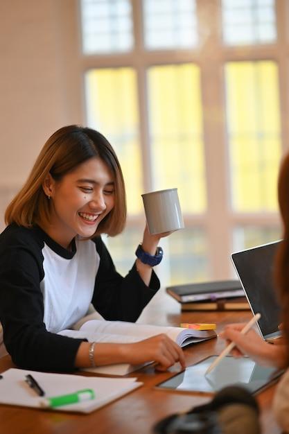 Jonge aziatische vrouwen tutoring vriend op houten lijst. Premium Foto