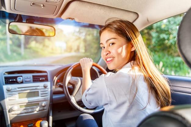 Jonge aziatische vrouwenbestuurder die een auto op de weg in platteland drijven Premium Foto