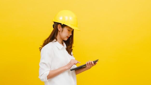 Jonge aziatische vrouweningenieur die digitale tablet met positieve uitdrukking gebruiken, gekleed in vrijetijdskleding en camera over gele muur bekijken. de gelukkige aanbiddelijke blije vrouw verheugt zich succes. Gratis Foto