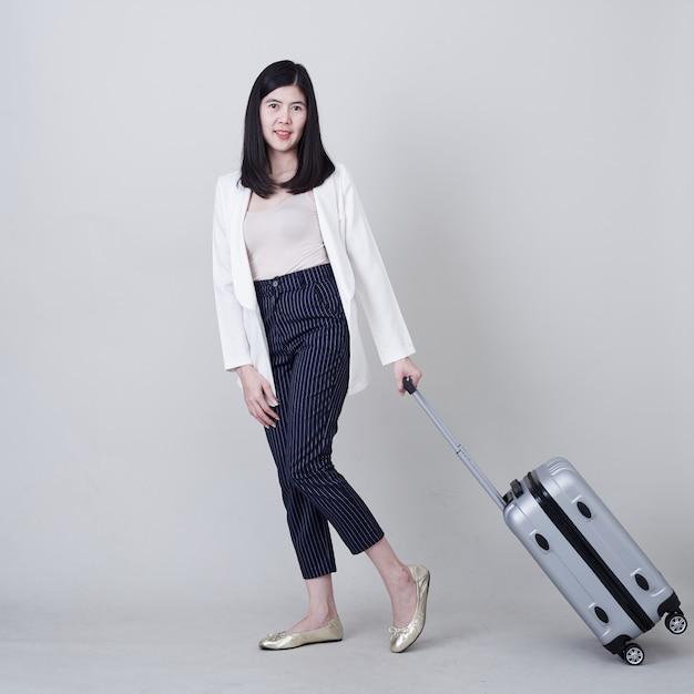 Jonge aziatische vrouwentoerist met bagage om te reizen Premium Foto