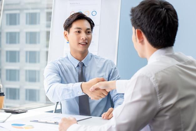 Jonge aziatische zakenman die handdruk met partner maakt Premium Foto