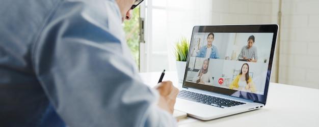 Jonge aziatische zakenman die laptop met behulp van praat met collega's over plan in videogesprekvergadering terwijl het werken vanuit huis in de woonkamer. zelfisolatie, sociale afstand nemen, quarantaine voor coronaviruspreventie. Gratis Foto