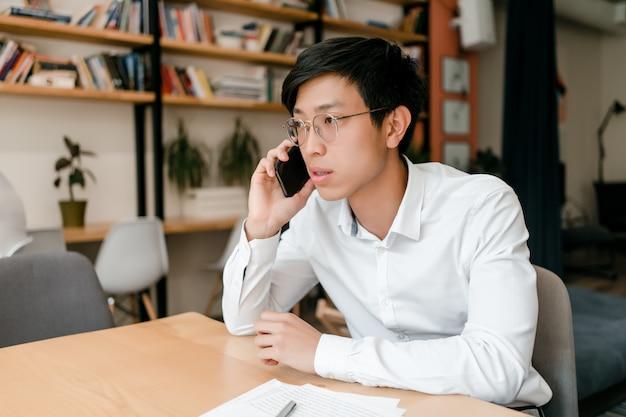 Jonge aziatische zakenman die op de telefoon spreken die zaken in het bureau bespreken Premium Foto