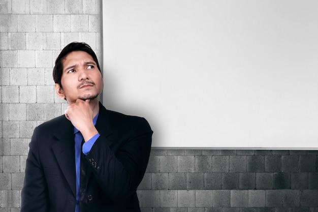Jonge aziatische zakenman die voor oplossing denkt Premium Foto