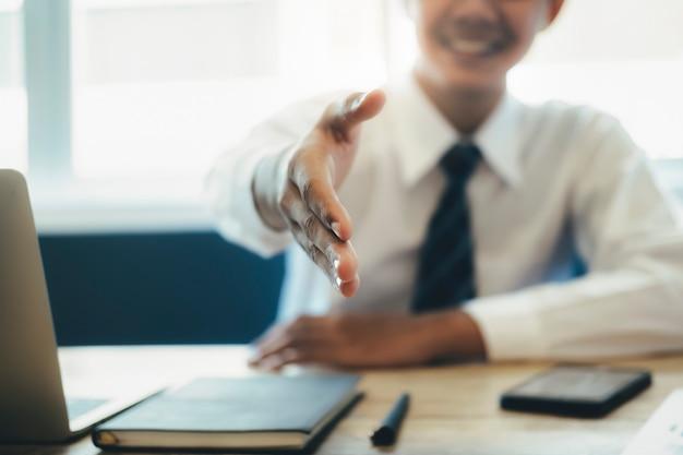 Jonge aziatische zakenman die zijn wapen in een handdruk uitbreidt. Premium Foto