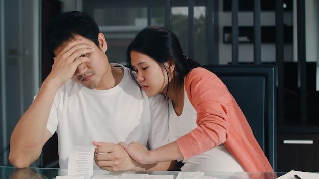 Jonge aziatische zwangere paarverslagen van inkomsten en uitgaven thuis. papa maakte zich zorgen, serieus, stress terwijl recordbudget, belasting, financieel document thuis in de woonkamer werkte. Gratis Foto