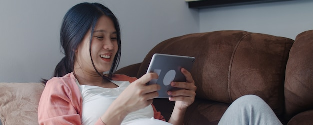 Jonge aziatische zwangere vrouw die de zwangerschapsinformatie van het tabletonderzoek gebruikt. mamma die het gelukkige positief en vreedzame glimlachen voelen terwijl zorg haar kind thuis liggend op bank in woonkamer. Gratis Foto