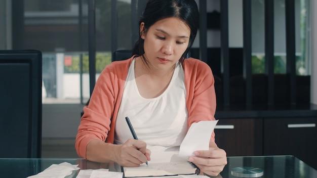 Jonge aziatische zwangere vrouw records van inkomsten en uitgaven thuis. mammameisje gelukkige gebruikende laptop verslagbegroting, belasting, financieel document, elektronische handel die in woonkamer thuis werken. Gratis Foto