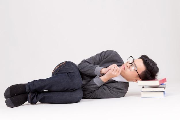 Jonge azië afgestudeerde studentenslaap met zijn boek Premium Foto