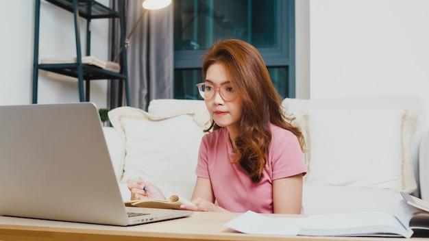 Jonge azië tiener meisje student afstandsonderwijs les met online leraar en studie op computer laptop in de woonkamer van huis 's nachts. sociale afstand nemen, quarantaine voor coronaviruspreventie. Gratis Foto