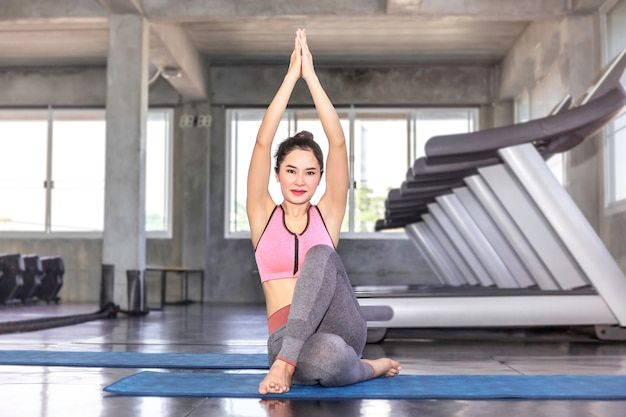 Jonge azië vrouw beoefenen van yoga met sportkleding beha en broek op fitness gym. Premium Foto