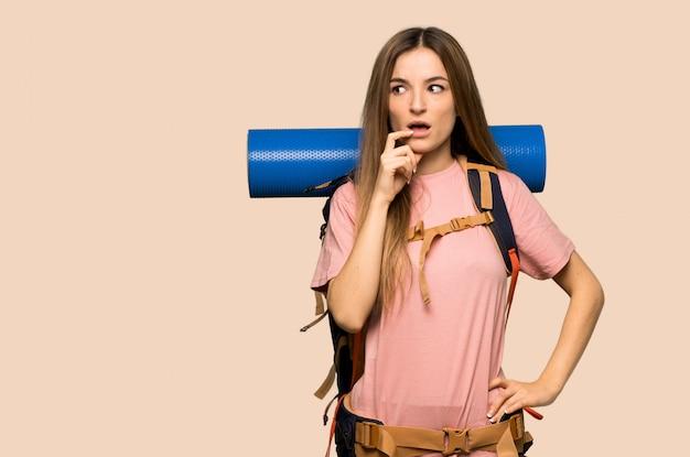 Jonge backpackervrouw die twijfels hebben terwijl omhoog het kijken Premium Foto