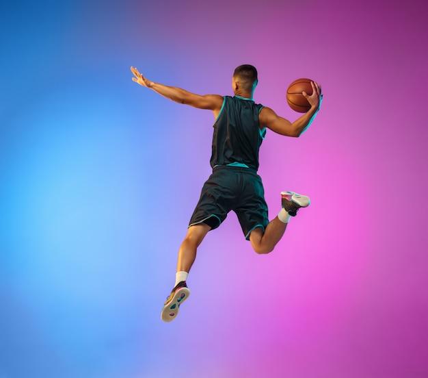 Jonge basketbalspeler in beweging op studio achtergrond met kleurovergang in neonlicht Gratis Foto