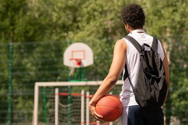 Jonge basketbalspeler met bal klaar voor spel staande op de rechtbank of speelplaats op zonnige dag Premium Foto