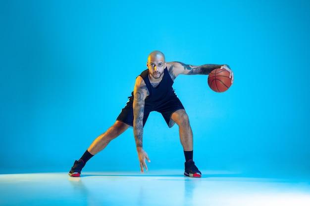 Jonge basketbalspeler van team dragen sportkleding training, oefenen in actie, beweging geïsoleerd op blauwe achtergrond in neon licht. concept van sport, beweging, energie en dynamische, gezonde levensstijl. Gratis Foto