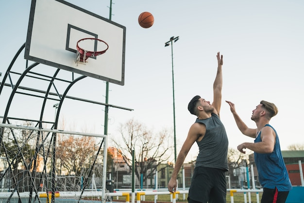 Jonge basketbalspelers spelen een-op-een op de buitenbaan. sport en basketbal concept. Gratis Foto
