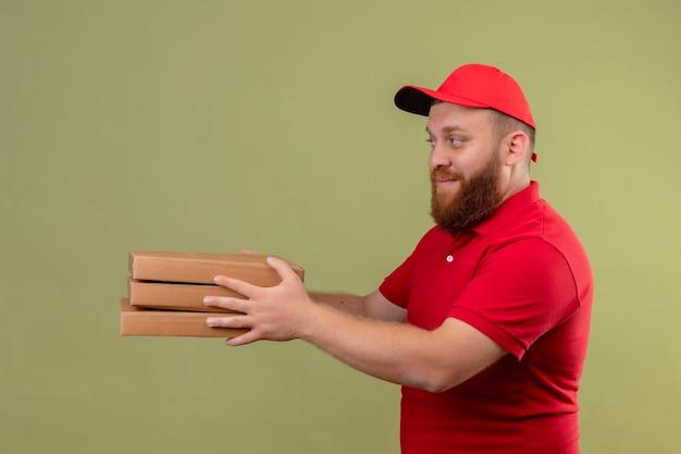 Jonge, bebaarde bezorger in rood uniform en pet die stapel pizzadozen geeft aan u klant vriendelijk lachend Gratis Foto