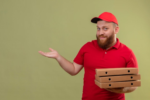 Jonge, bebaarde bezorger in rood uniform en pet met stapel pizzadozen die kopie ruimte met arm van zijn hand presenteren Gratis Foto