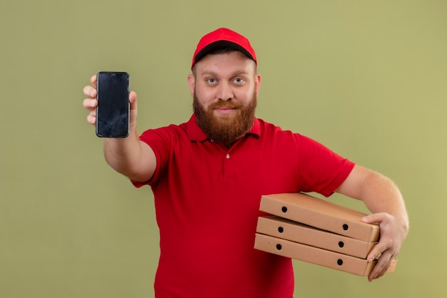Jonge, bebaarde bezorger in rood uniform en pet met stapel pizzadozen smartphone tonen aan camera op zoek zelfverzekerd Gratis Foto