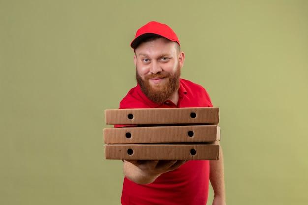 Jonge, bebaarde bezorger in rood uniform en pet met stapel pizzadozen vriendelijk glimlachen Gratis Foto