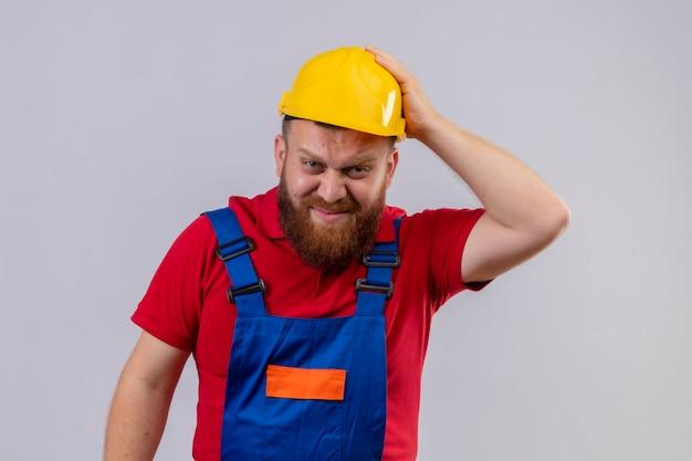 Jonge, bebaarde bouwersmens in bouwuniform en veiligheidshelm camera kijken verward en erg angstig met hand op hoofd voor fout Gratis Foto