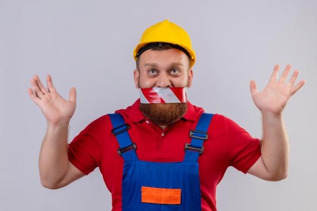 Jonge, bebaarde bouwersmens in bouwuniform en veiligheidshelm met band over zijn mond die het verhogen handen in sarrender opzoeken Gratis Foto