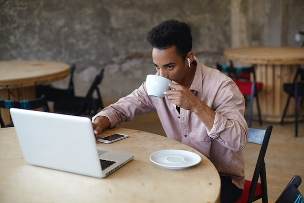 Jonge, bebaarde donkere zakenman met kort kapsel koffie drinken in het stadscafé tijdens het voorbereiden van materialen op zijn laptop voor een ontmoeting met klanten, zittend aan ronde houten tafel in beige overhemd Gratis Foto