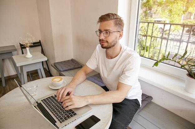 Jonge, bebaarde freelancer wit t-shirt en bril dragen, aan tafel in de koffieruimte zitten en laptop gebruiken, e-mails controleren en geconcentreerd kijken Gratis Foto