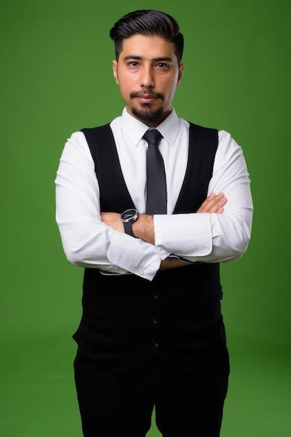 Jonge, bebaarde iraanse zakenman op groen Premium Foto