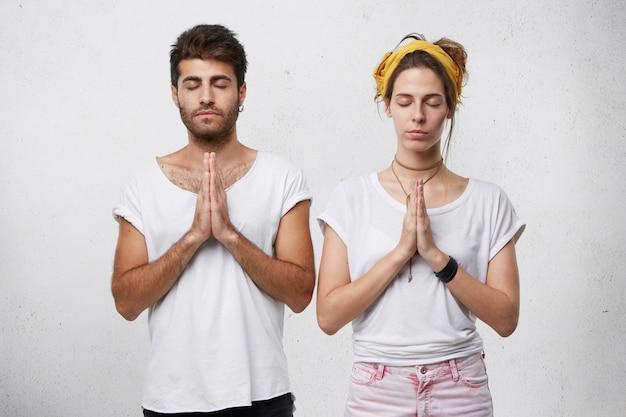 Jonge, bebaarde man en mooie vrouw mediteren binnenshuis, sluiten hun ogen en houden de handen bij elkaar en voelen ontspanning Gratis Foto