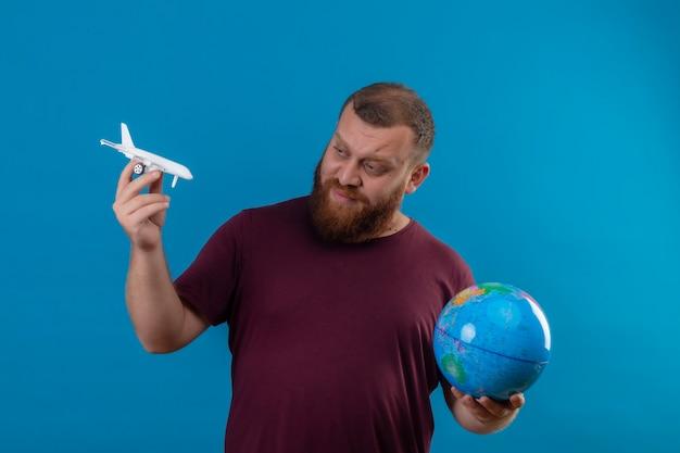 Jonge, bebaarde man in bruin t-shirt met globe en speelgoed vliegtuig speelgoed kijken met sceptische uitdrukking op gezicht Gratis Foto