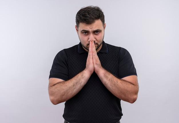 Jonge, bebaarde man in zwart shirt hand in hand zoals bidden bezorgd en emotioneel op zoek Gratis Foto