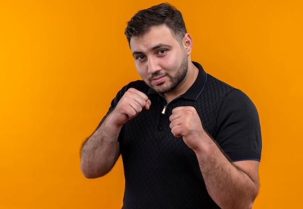 Jonge, bebaarde man in zwart shirt kijken camera poseren als een bokser balde vuist Gratis Foto