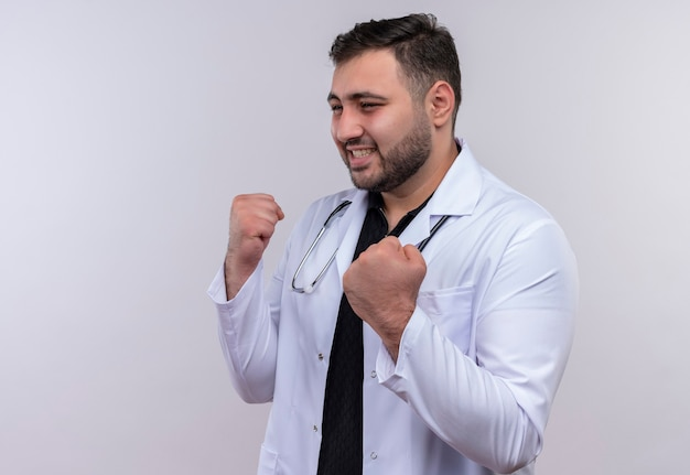 Jonge, bebaarde mannelijke arts dragen witte jas met stethoscoop opzij kijken poseren als een bokser met gebalde vuisten glimlachen, winnaar concept Gratis Foto