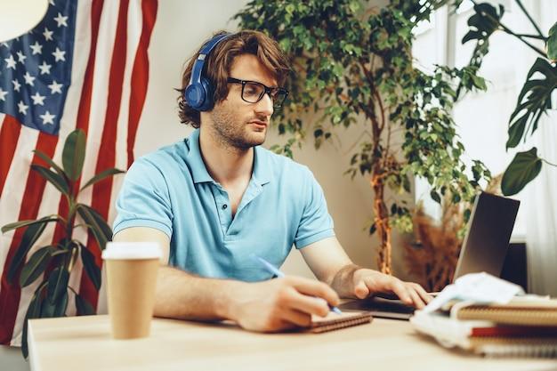 Jonge, bebaarde zakenman zittend aan tafel met laptop en amerikaanse vlag Premium Foto