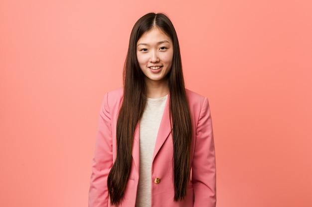 Jonge bedrijf chinese vrouw die roze gelukkig, glimlachend en vrolijk kostuum draagt. Premium Foto