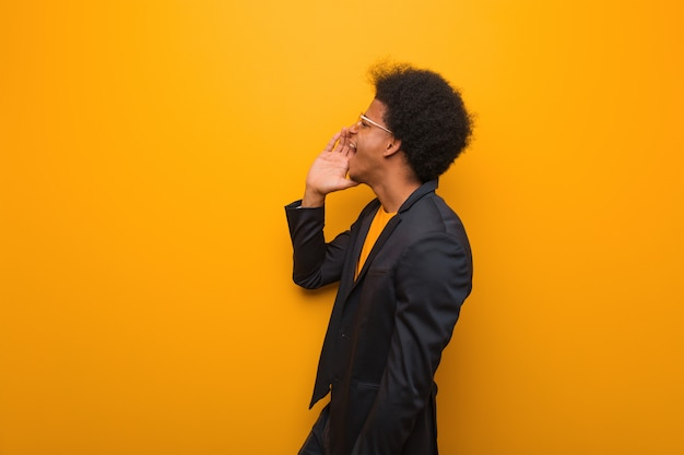 Jonge bedrijfs afrikaanse amerikaanse mens over een oranje ondertoon van de muur fluisterende roddel Premium Foto