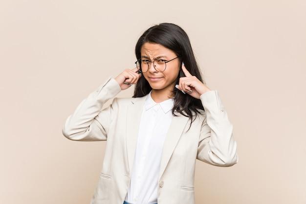 Jonge bedrijfs chinese vrouw die oren behandelen met handen. Premium Foto