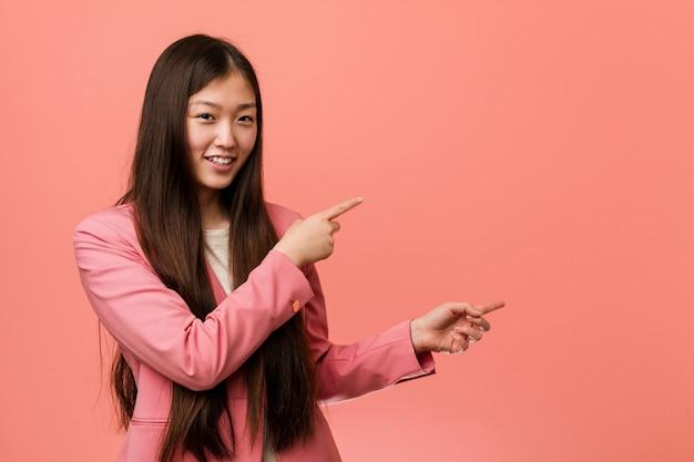 Jonge bedrijfs chinese vrouw die roze opgewekt kostuum draagt richt met weg wijsvingers. Premium Foto